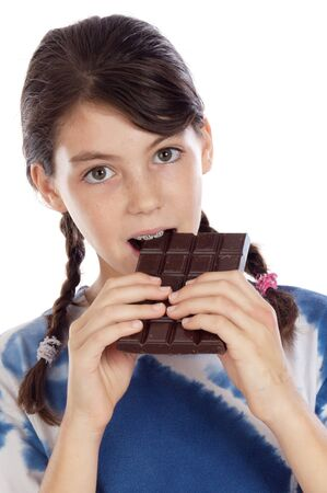 Adorable girl eating chocolate a over white background photo
