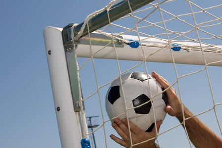 Photography of a Soccer ball in the goal net photo