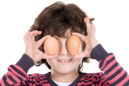 Adorable Child with two eggs on his eyes on a white background photo