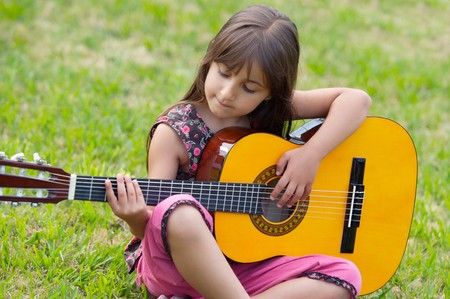 girl playing guitar: Girl with a guitar on the green grass