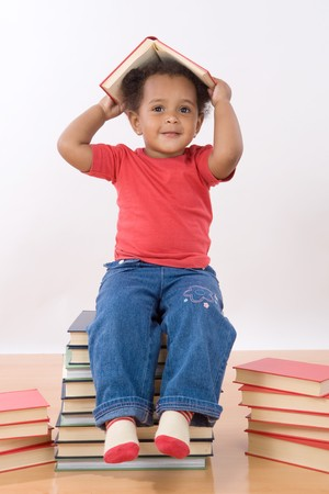 Adorable african baby sitting on a pile of books  photo