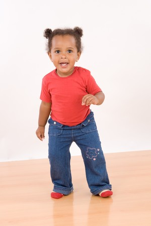 Adorable african baby dancing over wooden floor