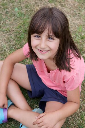Beautiful little girl with pink shirt sitting on the grass photo