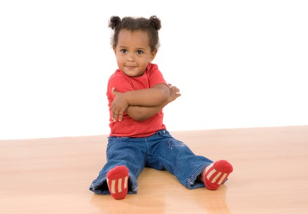 Adorable african baby sitting on wooden floor isolated over white