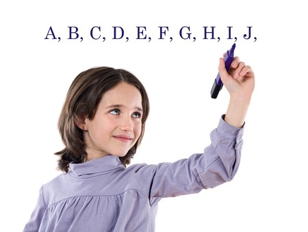 Adorable girl writing the ABC with fluorescent on a over white background