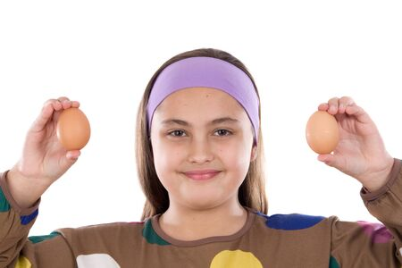 Adorable girl with two eggs on her hands on a white background photo