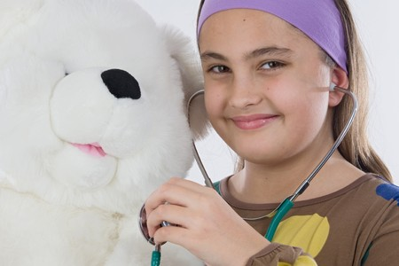 Little doctor smiling and examining her teddy Stock Photo - 4402862