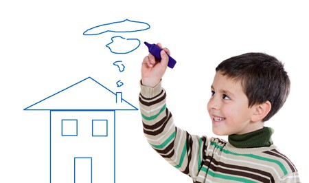 Adorable boy drawing a house on a over white background photo