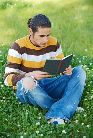 Casual boy reading a book in the green grass photo