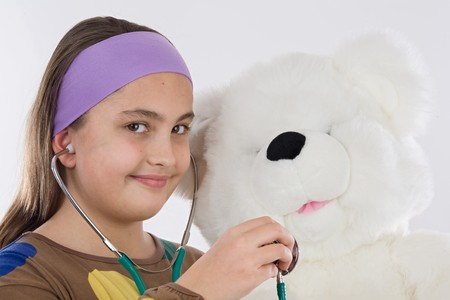 Little doctor smiling and examining her teddy photo