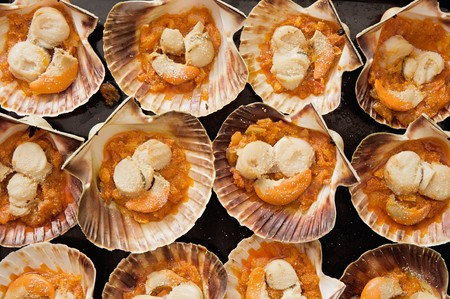 Baking tray of scallops cooked with tomato sauce photo