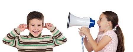 Little girl shouting through megaphone at a boy isolated over white  photo