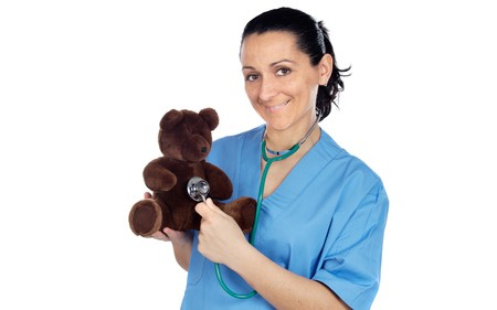 Adorable doctor with a teddy bear in her arms a over white background photo