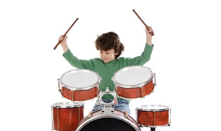 Beautiful boy playing the drums on a white background photo