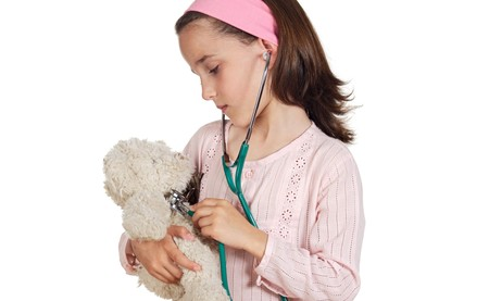 Little doctor examining her teddy bear on a over white background photo
