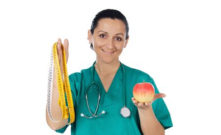 Pretty woman doctor with an apple and tape measure on a over white background photo