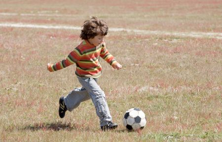 kids playing outside: Small child playing football in the field