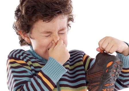 Cute young boy with stinky shoe pitching his nose Stock Photo - 4635284