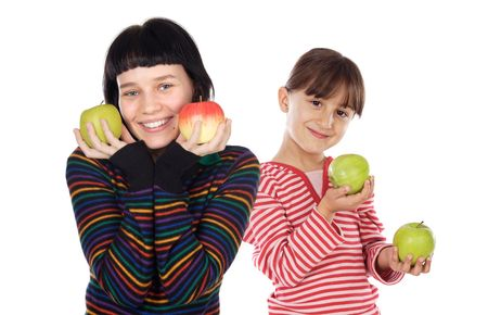 Couple of little girl and her sister with apples in the hands a over white background photo