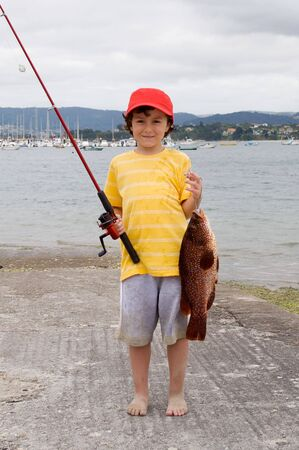 Child fisherman with red hat, a great catch! photo