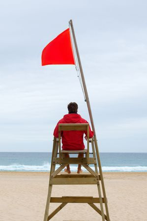 Lifeguard sitting in his chair watching the sea Stock Photo