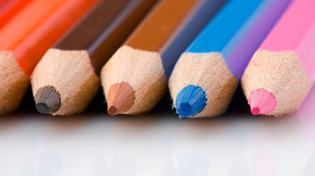Pencils of many colors aligned with reflection on floor photo