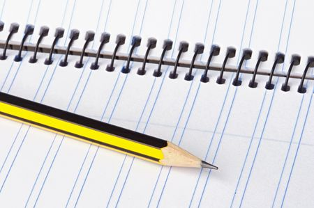 pencil and notebook over a white back ground photo
