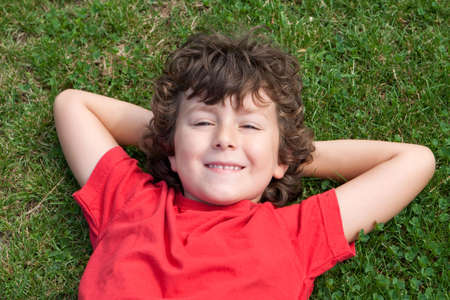 lied: Happy child lied down on the grass with red shirt Stock Photo