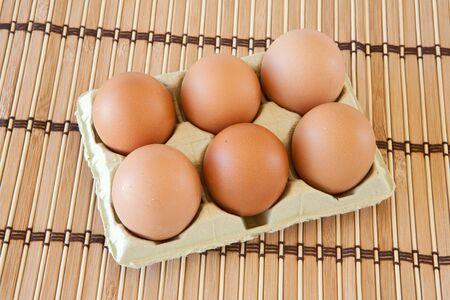 Photo of half dozen eggs on bamboo tablecloth photo
