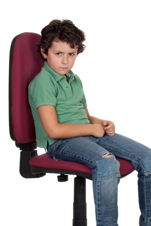 sulking: Angry little boy sitting on big chair isolated on white. Stock Photo
