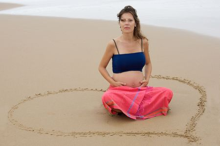 Beautiful pregnant girl on the beach sitting in a heart photo