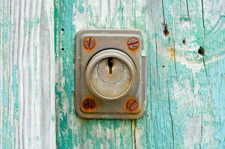 Rusty lock by a weathered green door photo