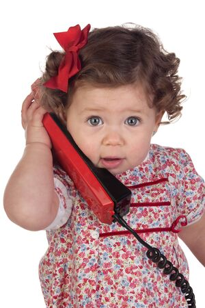 Funny baby girl with red telephone isolated over white background photo