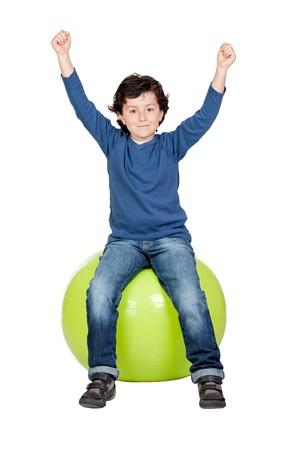 Niño sentado sobre una bola de pilates aislada en un fondo blanco Foto de archivo