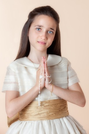 Pretty girl on the day of their communion in prayer with the rosary in his hands photo