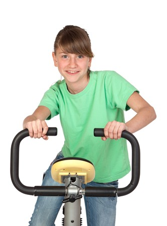 static bike: Funny teenage girl practicing bike isolated on white background