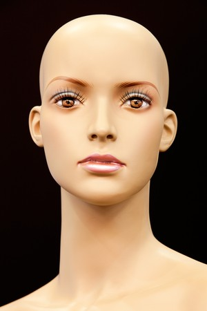 Face of a bald mannequin isolated on black background photo