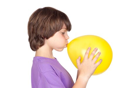 Funny boy blowing up a yellow balloon isolated on white background  photo
