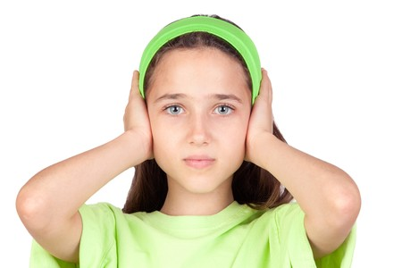 noise isolation: Frightened girl with ears plugged isolated on a white background Stock Photo