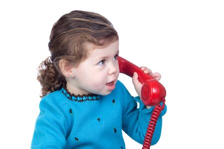 Beautiful baby girl with a red telephone isolated over white background photo