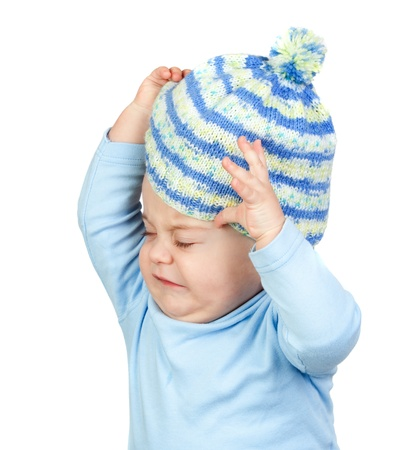 Angry baby taking off a wool cap isolated on white background Stock Photo - 8639128