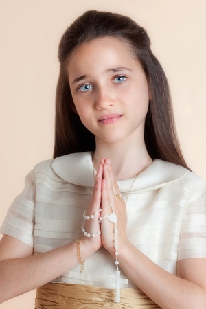 Pretty girl on the day of their communion in prayer with the rosary in his hands Stock Photo - 8822064
