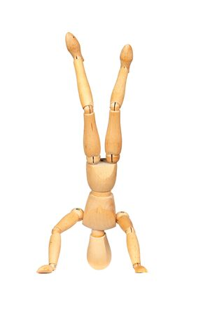 Jointed wooden mannequin doing handstands isolated on white background photo