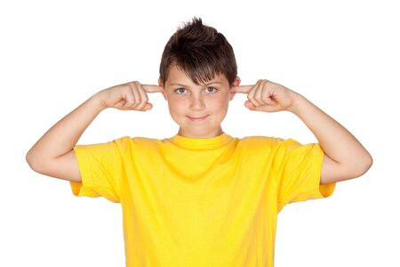noise isolation: Funny child with yellow t-shirt covering ears isolated on white background Stock Photo
