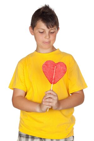 Funny child with yellow t-shirt with a big lollipop isolated on white background photo
