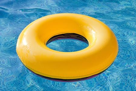 Geel vlotter drijvend in het zwembad met blauwe water