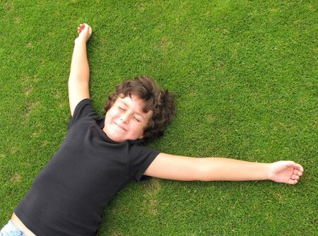 Happy child resting on a beautiful green grass                               photo