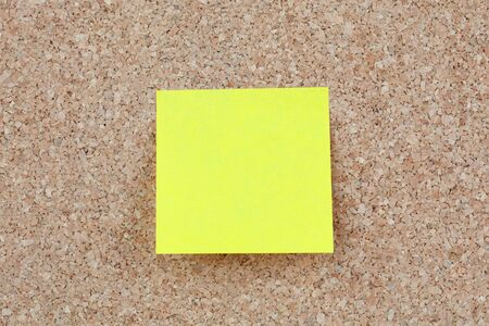 Photo of corkboard with a yellow post-it photo