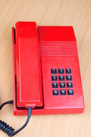 Red classic telephone on a wooden surface photo