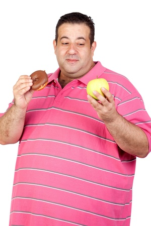 Fat man deciding between a candy and an apple isolated on white background